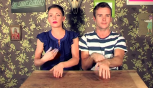 A woman and a man sit at a wooden table, performing complex Irish dance moves with both hands