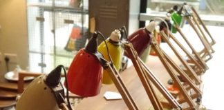 A row of colourful vintage lamps are lined up along a table as part of an exhibition at Midcentury East furniture show