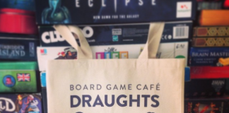 A tote bag with the Draughts café logo hangs in front of stacks of board games