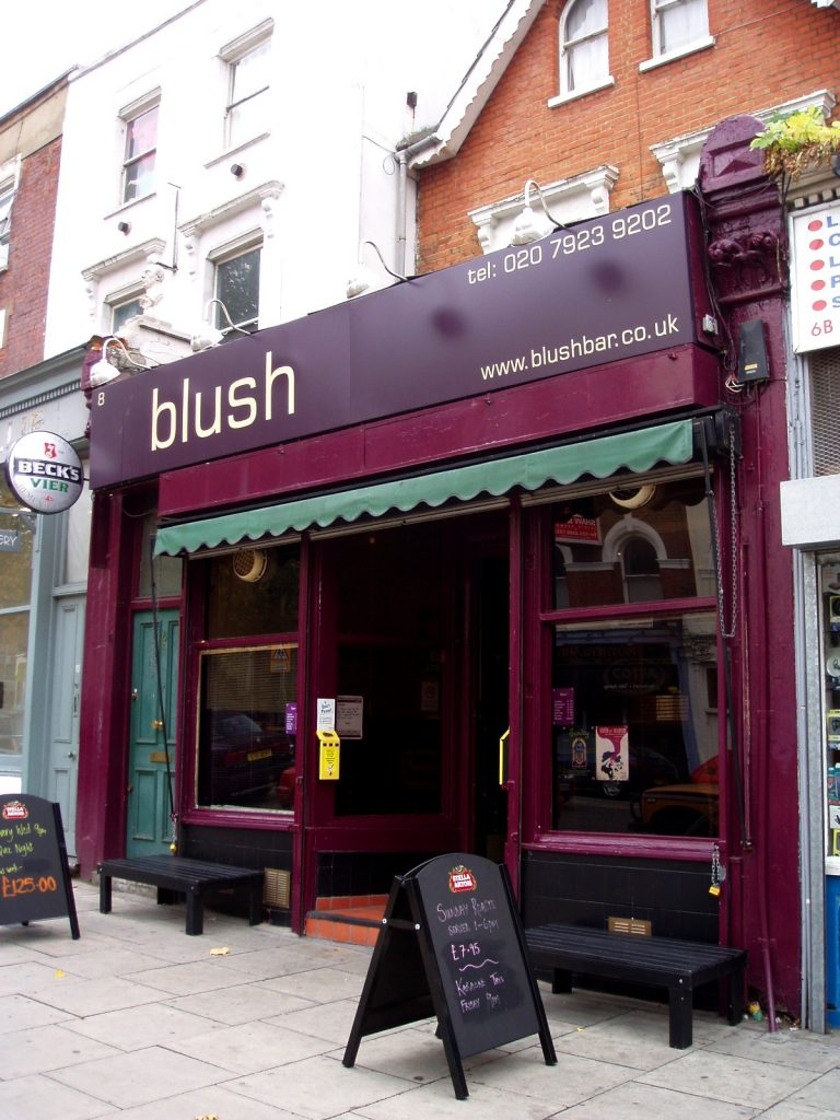 A shot of the exterior of LGBT venue Blush Bar, painted dark crimson with a black sandwich board on the pavement outside