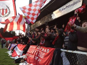 An image of Clapton FC fans waving flags and chanting.