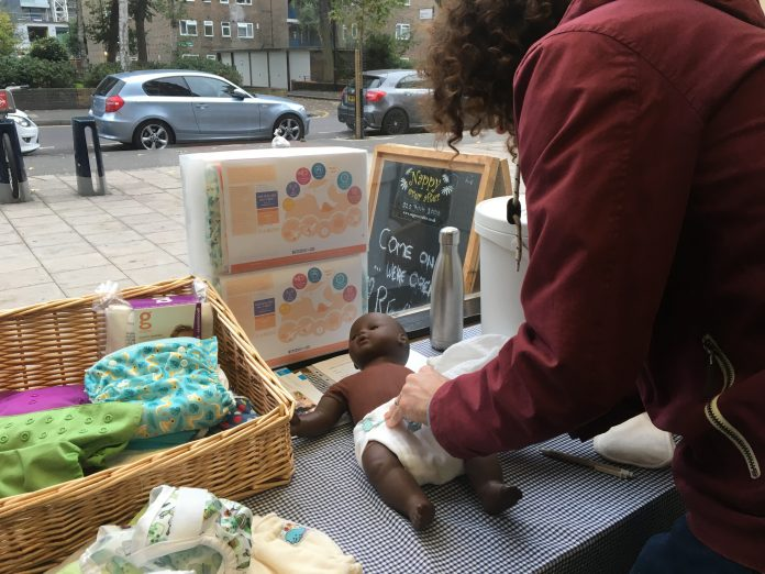 A customer demonstrates how to put a nappy on a child